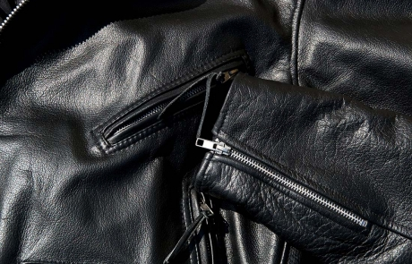 High contrast close up of black leather motorcycle jacket showing zippered pockets and portion of  sleeve in sunshine.